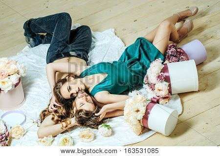 Sexy couple young beautiful cute lovers in love pretty girl and sexi man lying on back on white bedsheet among flowers on wooden floor