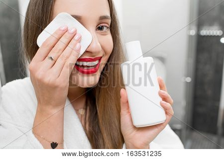 Woman removing makeup with cotton swab in the bathroom. Young girl taking care of skin