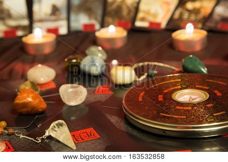 Moscow, Russia - December 4, 2016: Chinese magnetic compass - Luopan. Tarot cards, candles and minerals. Feng Shui background