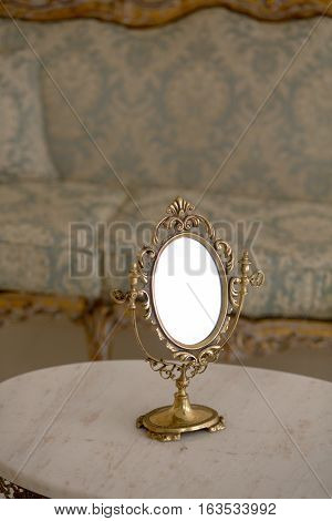 Closeup of vintage mirror represented on table in royal apartment. Royal golden frame on table in vintage interior.