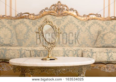 Royal golden frame on table in vintage interior. Closeup of mirror represented on table in royal apartment. Royalty concept.