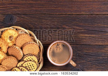 Cup of hot coffee and various cookies in plate on dark wooden table top view. Space for text