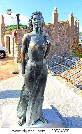 TOSSA DE MAR, SPAIN - OCTOBER 06, 2014: Bronze statue of Ava Gardner in Tossa de Mar, Spain. Monument to the renowned American actress was opened within the Vila Vella in 1992
