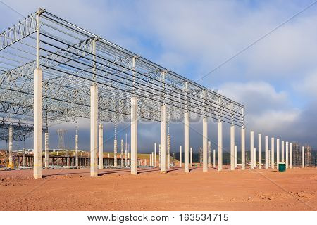 Construction building new warehouse factory halfway concrete columns with steel roofing beams