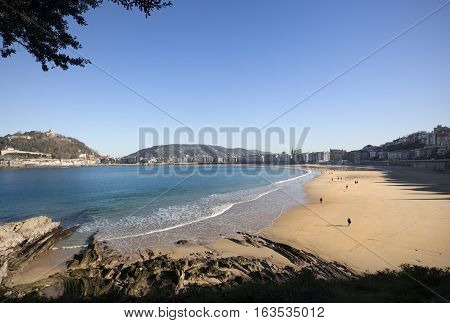 DONOSTI-DECEMBER 22 2014: On sunny days the people of Donosti take the opportunity to stroll along La Concha Beach in Donosti, Spain on December 22,  2014