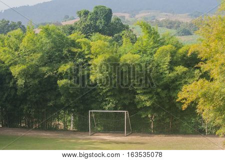Soccer goals with trees surrounded it in natural.
