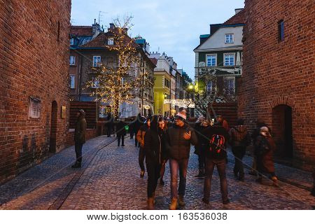 Warsaw, Poland - December 25th, 2016. Tourist walking on the Barbican fortress wall near Christmas decorations at the Warsaw Old town by Xmas night.