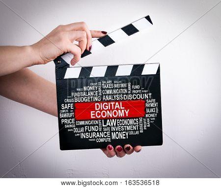 Digital Economy Concept. Female hands holding movie clapper.