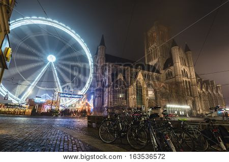 Ghent, Belgium - December 27th, 2016. Gent city winter festival in Flanders. Christmas fair with ferris wheel and bikes near Saint Nicholas Church on the Ghent Old town square by New Year holidays.