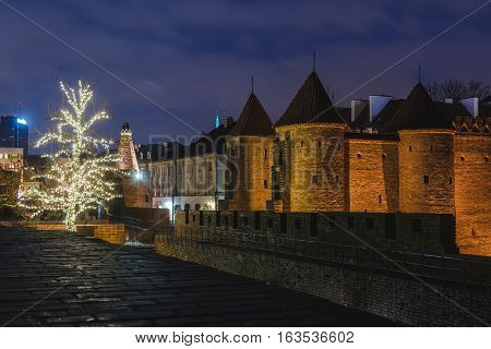 Warsaw, Poland - December 25th, 2016. Barbican fortress wall and Christmas decorations at the Warsaw Old town by Xmas night.