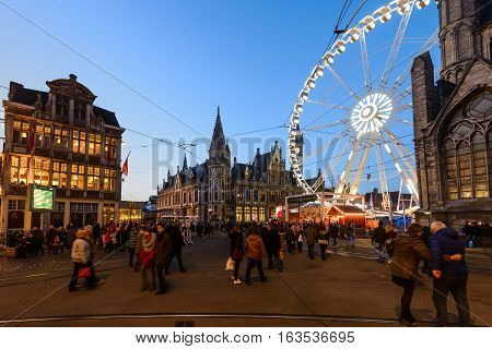 Ghent, Belgium - December 27th, 2016. Gent city winter festival in Flanders. Christmas fair with ferris wheel and festive decorations surrounded by historical buildings on the Ghent Old town square.