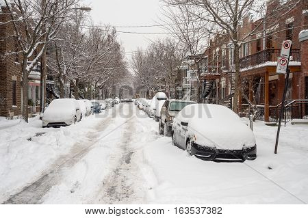 Street in Montreal's Plateau Neighbourhood with cars covered in snow