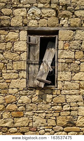Old Window With Broken Wooden Shutter On A Stone Building