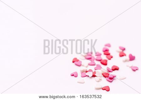 several small hearts in white pink and red on a white background. festive background for Valentine's day birthday holiday wedding