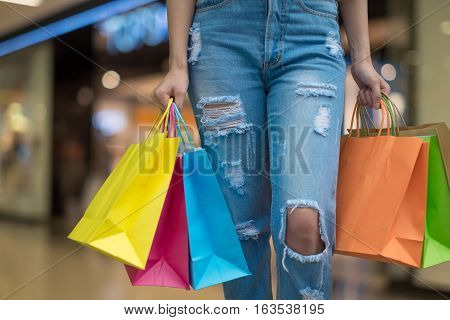 Happy beautiful woman with shopping bags stands at shop. Attractive caucasian girl with purchasing bags in big mall