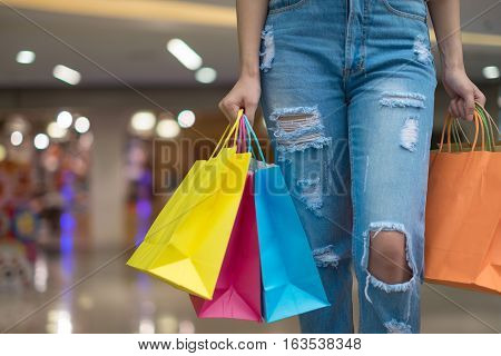 woman wearing muted, gentle colours holds five colourful, patterned shopping bags