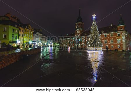 Warsaw, Poland - December 24th, 2016. Warsaw old town at winter night before Christmas and New year holidays. The Royal Castle, Xmas tree and market square surrounded by historical buildings.
