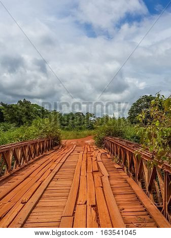 Dodgy red stained wooden bridge with timber planks and old iron rails crossing river in Gabon, Central Africa