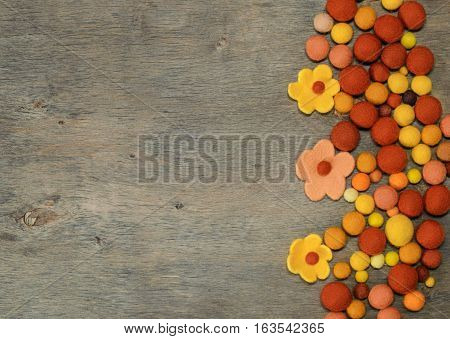 multicolored felted beads and yellow flowers on the wooden background with space for text