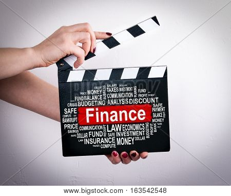 Finance Concept. Female hands holding movie clapper.