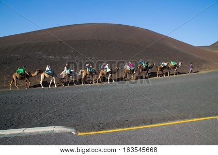 Tourists riding camels in Timanfaya National Park. Lanzarote Canary Islands. Circa December 2016