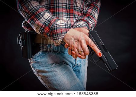 woman wearing jeans and shirt holding a gun