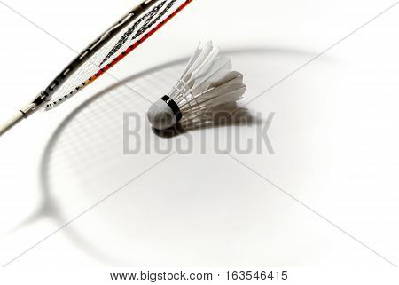 Shuttlecock and badminton racket shadow on white background