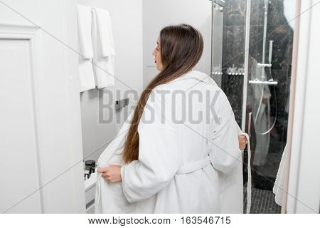 Woman taking off the bathrobe going to the shower in the bathroom