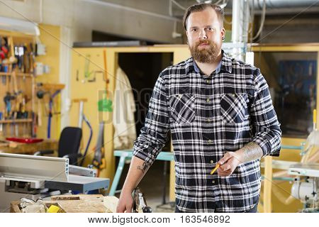Carpenter designs and prepares new work. Smiling adult craftsman in a work shop for wood work and construction.