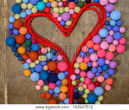 red heart and multicolored beads made of wool merino on the wooden background. Heart silhouette