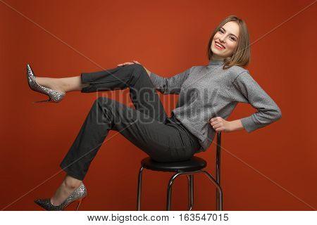 Style In Grey. Office Look.  Model Is Posing On The Orange Backg