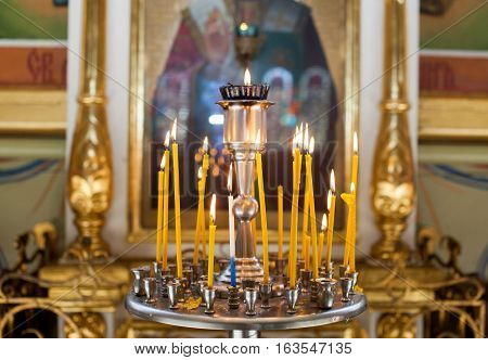 Church candles standing in the temple on the stand during the service. Religious Orthodoxy and Catholicism symbol.