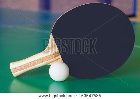 Black wooden racket for ping pong and white ball lying on the green table.