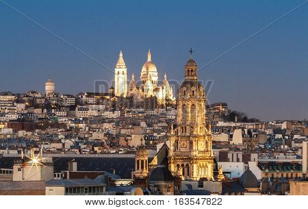 The basilica Sacre Coeur and parisian houses and Saint Trinity church in the foreground Paris France