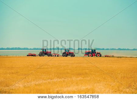 Summer day three tractors to plow plow the soil on sloping cornfield. Agricultural land treatment before planting.