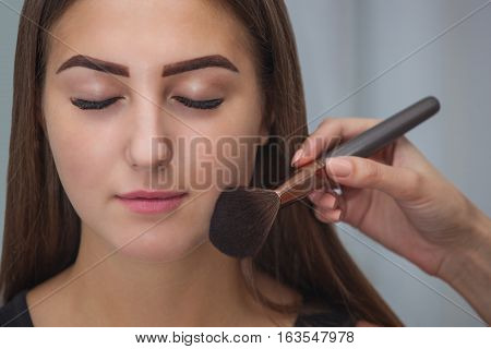 Master inflicts brush powder on the face of the girl completes the day make-up in a beauty salon. Professional skin care.