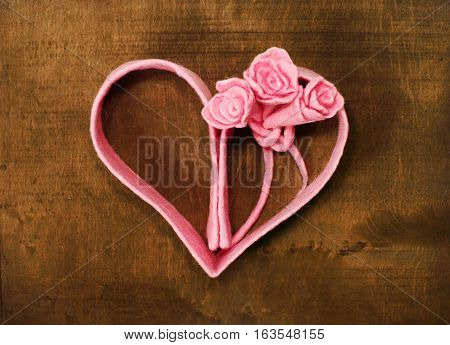 Bouquet of roses and heart silhouette on the wooden background
