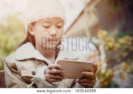 Young asian girl in winter suit playing on cellphone in relax time looking cute when her texing on phone vintage filtered.