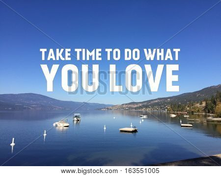 Inspirational quote in white text over calm summer lake with bright clear blue sky and lake water. Boats anchored and buoys on water. Mountains in background and reflections on water.