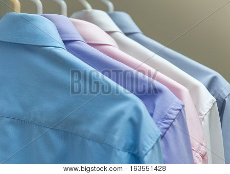 bright men's shirts hanging on hangers gray background stock photo