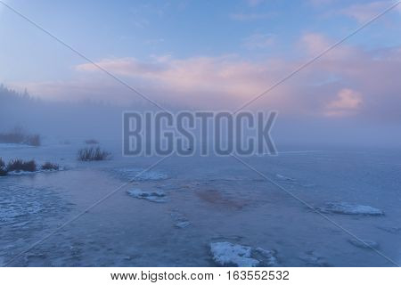 Winterscape scenic of clouds at dusk over a frozen lake