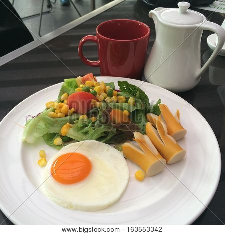 American Breakfast Egg sausages and salad in the cafe