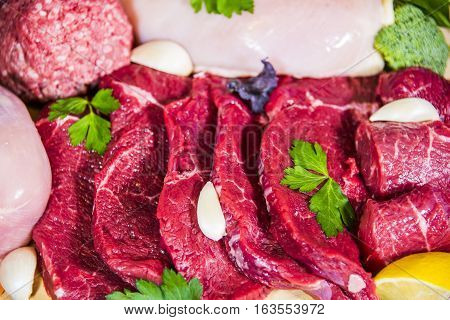 Fresh Raw Meat Background with Beef Meat Turkey and ground beef, Raw meat, and fresh chicken layered and plated surrounded by broccoli, lemons,and topped with fresh parsley leaves and garlic.
