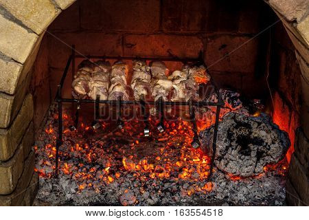 Burning fireplace and barbecue pork at home.