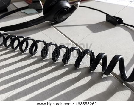 Customer service call center abstract spiral cord in sunshine at office cubicle workplace with headset in background for phone call sales or tech support image with copy space