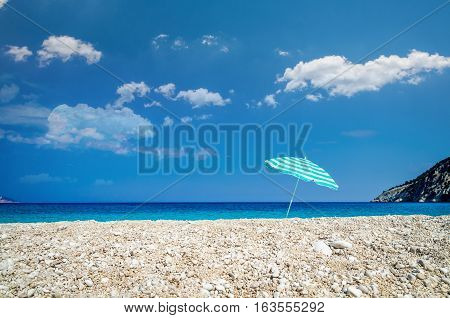 Beach umbrella on sunny Myrtos beach, the ionian sea in backgrou. Blue with white parasol on a Greek beach.