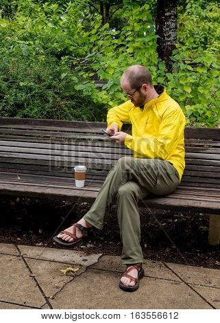 Man in Yellow Jacket Checking His Email on a park bench