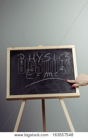 poster of Handwritten physics word and formula E=mc2 on chalkboard gray background