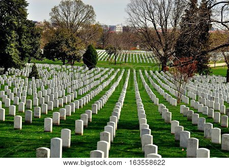 Arlington Virginia - April 12 2014: Row upon row of military gravesites on a hilly at Arlington National Cemetery *
