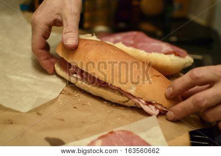 Making classic Italian pannini sandwich with fresh cold cuts mortadella and capicollo